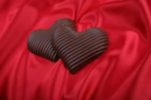 Chocolate hearts on red satin backdrop