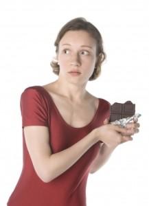 Woman eating choc guilty look